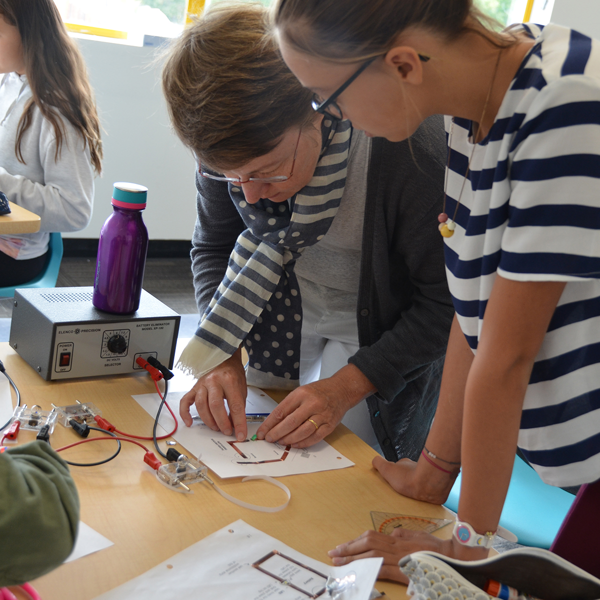 A teacher helping a student with circuits