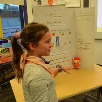 Girl explaining her science fair project.